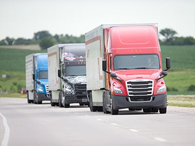 Crete, Shaffer, and Patriot Fleet trucks on road